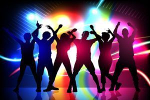 silhouettes of party people dancing on stage with disco light