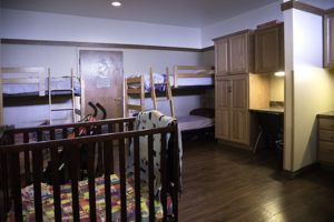client bedroom with bunk beds, a crib and personal desk and storage cabinet