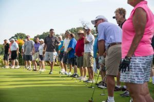 a line of golfers ready to putt